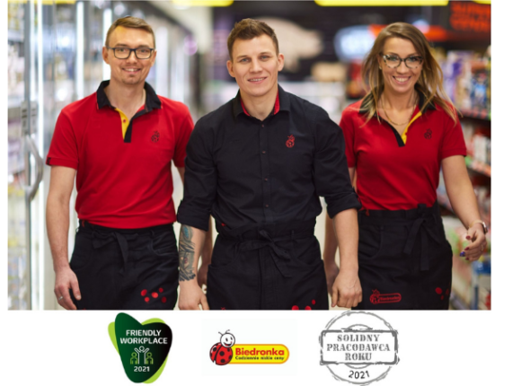 trzech pracowników sklepu z kierownikiem na środku oraz logo nagród